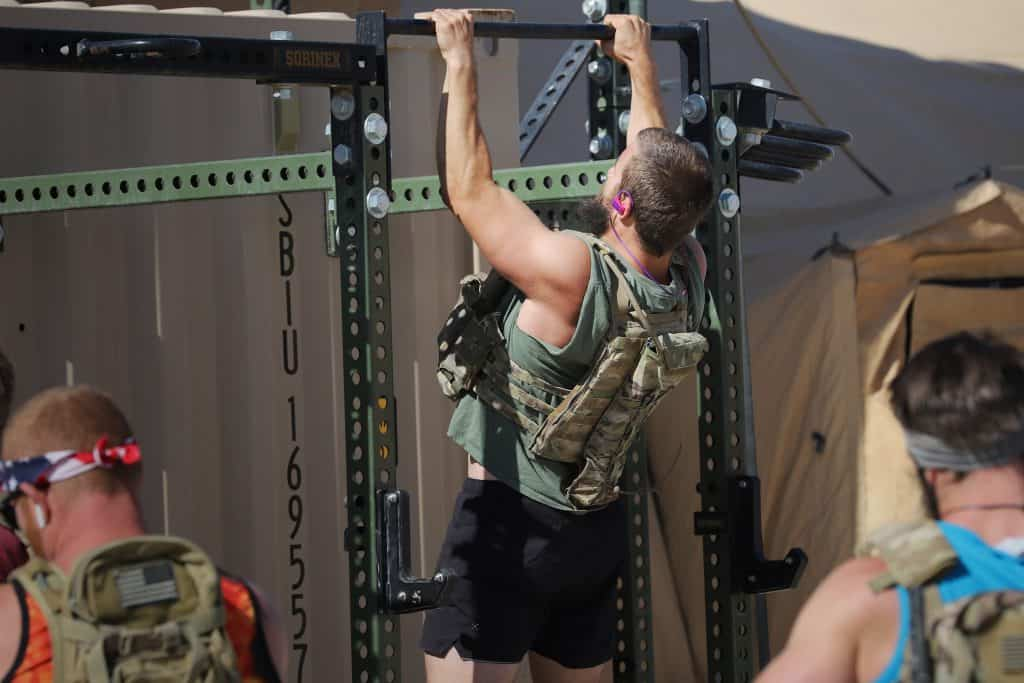 """Army Special Operations Forces members perform the """"Murph"""" workout for Memorial Day on May 25, 2020, during a deployment to At-Tanf Garrison, Syria. The workout consists of a one-mile run, 100 pull-ups, 200 push-ups, 300 squats, and another one-mile run, completed consecutively while wearing a weighted tactical vest. (U.S. Army photo by Staff Sgt. William Howard)"""