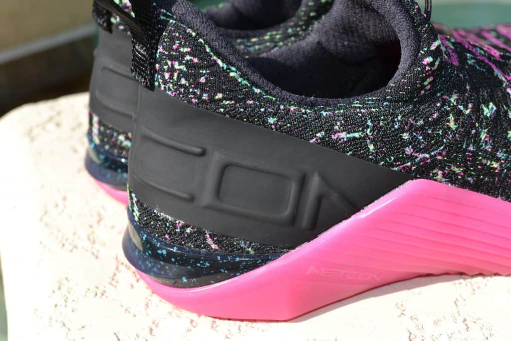 Heel closeup of the Nike React Metcon AMP Training Shoe - Black/Fire Pink/Green Strike/Blue Fury (with Glow-In-The-Dark Sole)