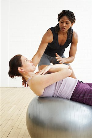 A personal trainer working with a fitness enthusiast on a balance ball
