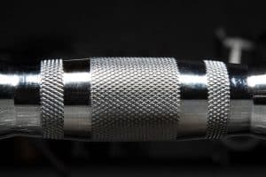 Close-up of the knurl on a Rogue Fitness Rubber hex dumbbell - the handle is chrome plated for oxidation and corrosion resistance.