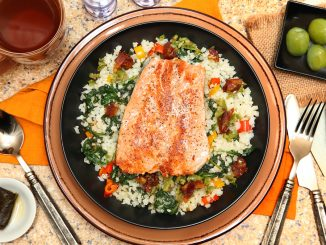Salmon with Riced Cauliflower and Vegetable Salad at table with hot Tea and castelvetrano olives. This meal is both Whole30 diet and Paleo approved.