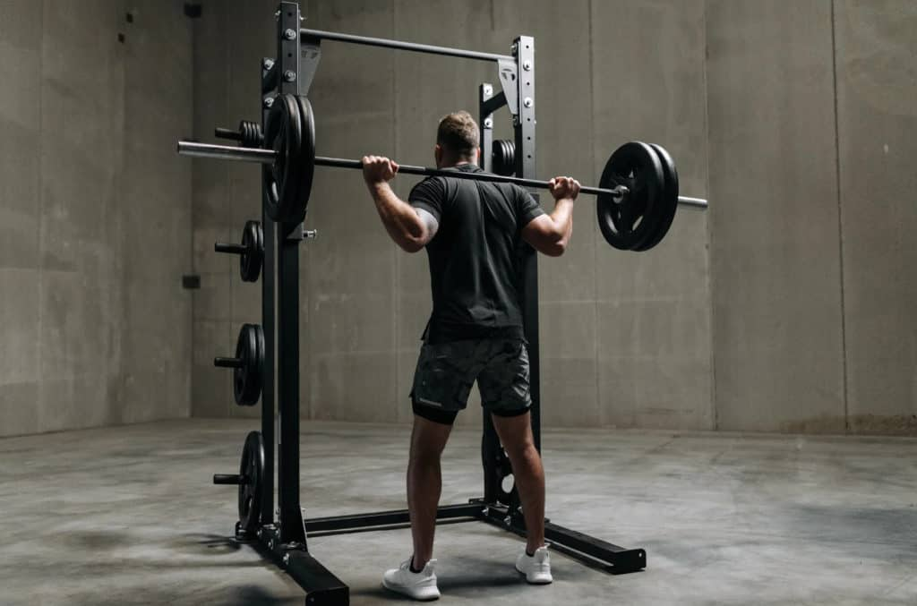 Torque USA Wall-Mounted Squat Rack Slim with a user 1