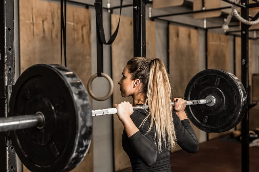 Young woman working out with a barbell, using the squat exercise.