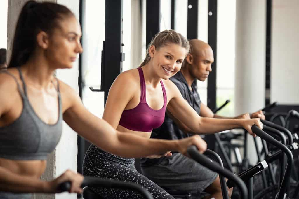 Fit woman working out with class on stationary bike at gym. Portrait of young beautiful woman smiling and looking at camera while cycling. Happy cheerful athletes in a row training on exercise bike.