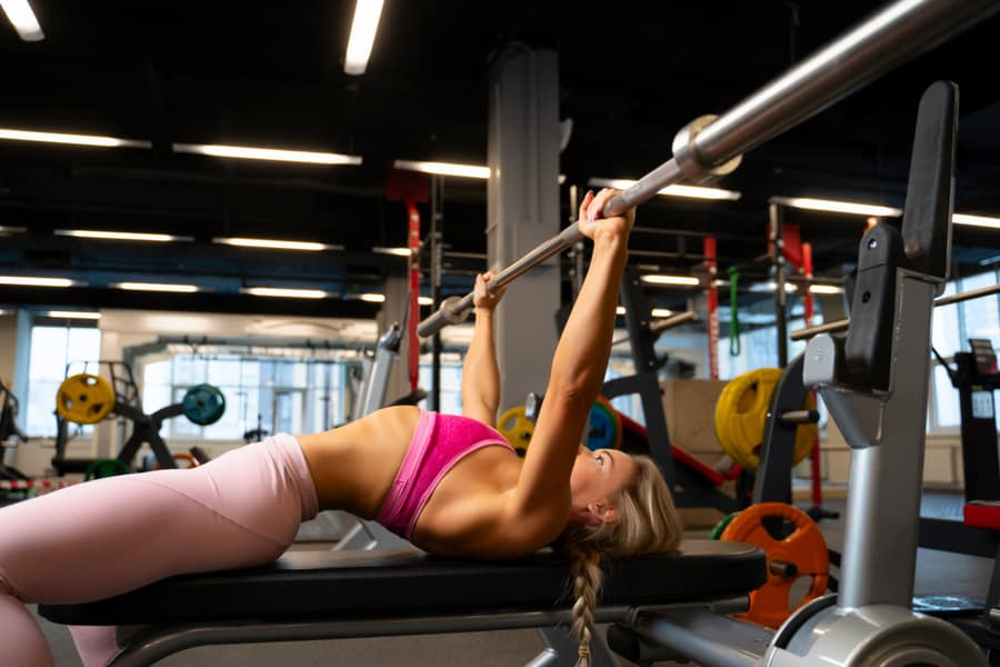 Woman performing bench press with a properly arched back.
