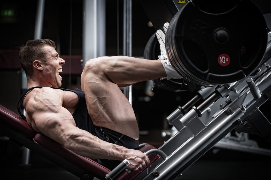 Bodybuilder using the leg press machine