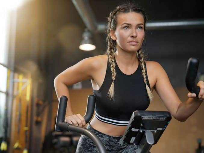 Young woman working out with an air bike.