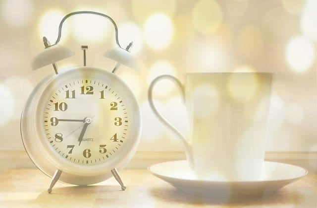 A steaming cup of fresh coffee shown with an alarm clock - good morning!