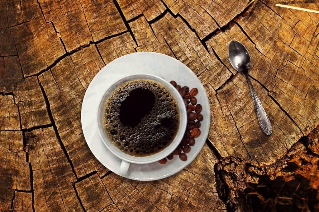 A coffee cup, with black coffee, and a spoon, on a table-top.