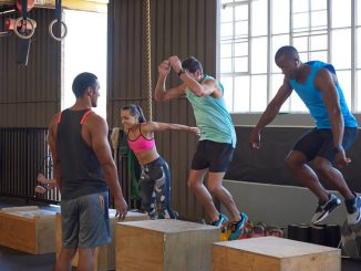 A CrossFit coach oversees a group of trainees performing the box jump.
