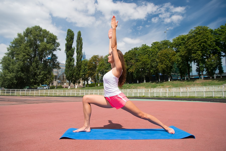 Woman performing yoga warrior pose outdoors