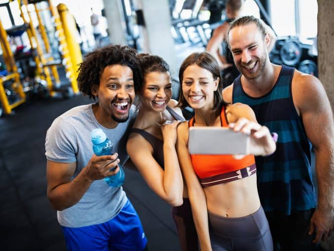 A group of fitness enthusiasts taking a selfie in the gym