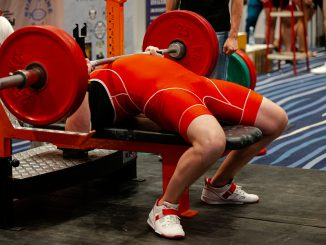 Heavy bench press on a flat bench with Olympic barbell.