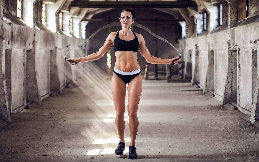 Woman jumping rope in abandoned warehouse