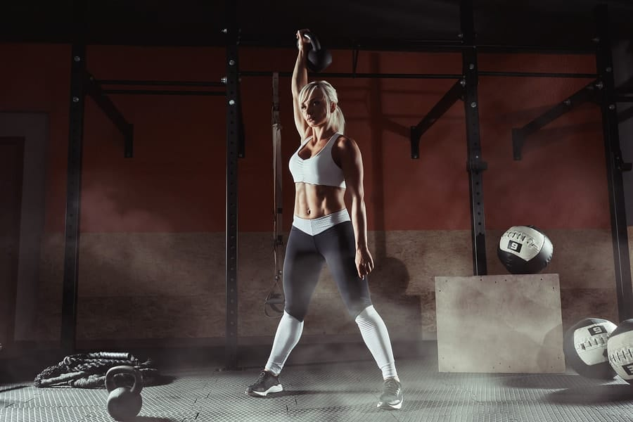 Hoisting a kettlebell overhead - great single limb workout that builds strength, power, balance, and stability