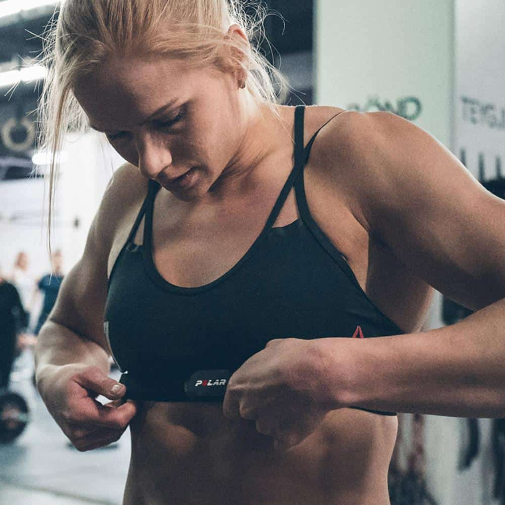 Female athlete using a chest strap heart rate sensor