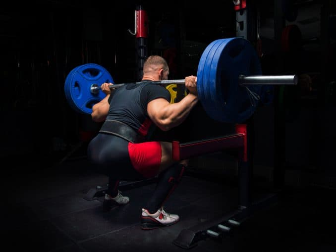 A weightlifting belt being worn for a set of heavy barbell squats.