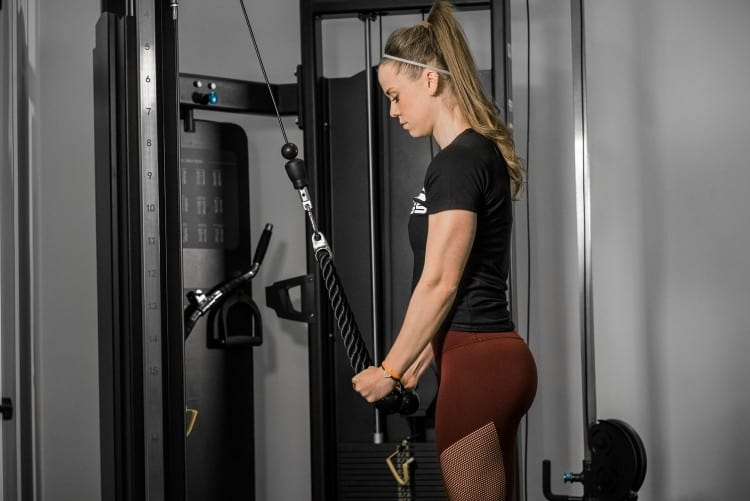 A trainee uses a cable attachment for perform the triceps pushdown on a functional trainer machine.
