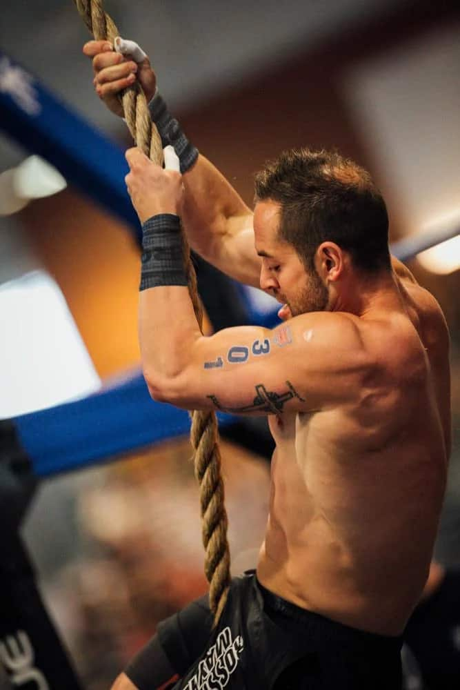 Rich Froning using Rogue Wrist Bands to keep his grip dry during a CrossFit competition.