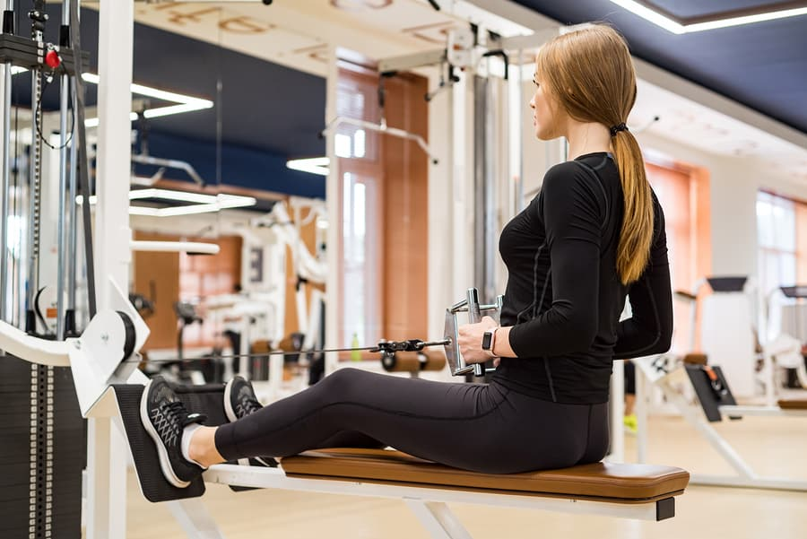 A woman performing a low row exercise on a machine in the gym.