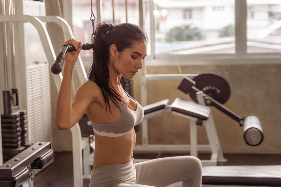 A woman performing the lat pulldown exercise on a machine in a gym.