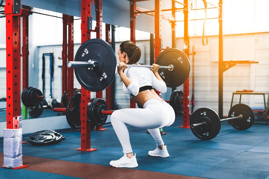Woman performing the barbell squat in a gym