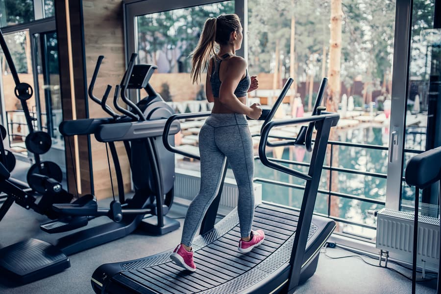 Young woman running on a curved treadmill in the gym.